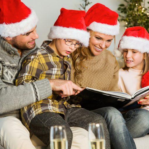 família feliz na noite de natal olhando álbum de fotos